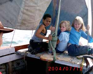 3 kids sitting in a boat